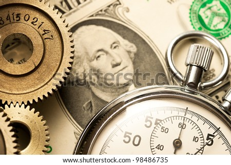 Mechanical ratchets, stopwatch and dollar - stock photo