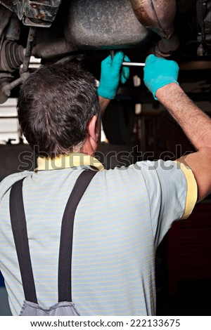 Mechanical repairs a car in the garage, unscrew a bolt. - stock photo