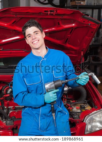 Mechanical smiling and holding a tool in a garage - stock photo