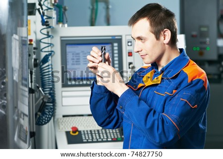 mechanical technician checking cutting detail after cnc milling machine center at tool workshop - stock photo