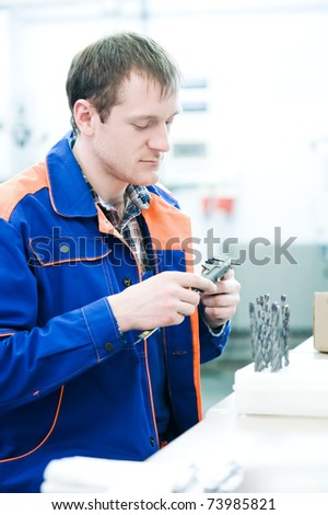 mechanical technician measuring detail after cnc milling cutting machine center at tool workshop