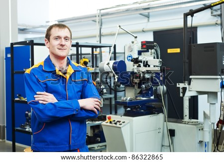 mechanical technician near milling machine at tool workshop