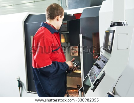 mechanical technician service engineer worker at cnc metal machining milling center in tool workshop - stock photo