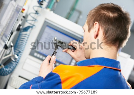 mechanical technician worker measuring detail tool after processing on cutting machine center at workshop - stock photo