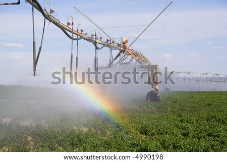 Mechanical watering system creates a rainbow over the field - stock photo