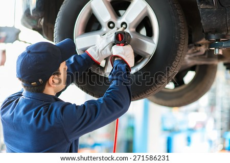Mechanician changing car wheel in auto repair shop - stock photo