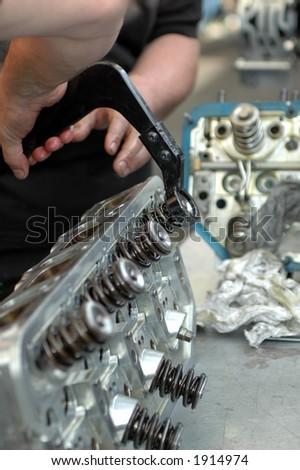 Mechanics adjusting engine parts - stock photo