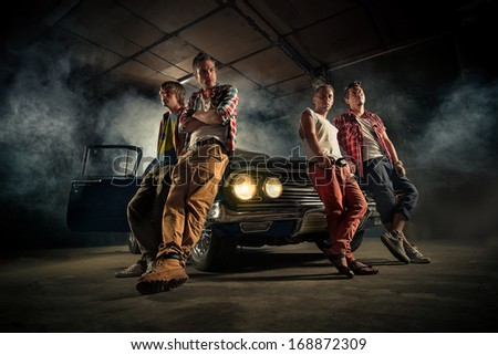 Mechanics at a garage repairing the retro car in smoke - stock photo