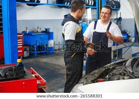 Mechanics at car service - stock photo