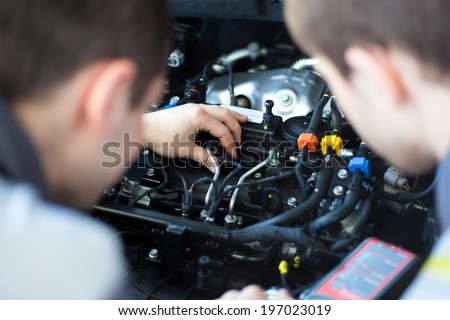 Mechanics at repair shop. Top view of two confident mechanics working on a car engine. Selective focus. - stock photo