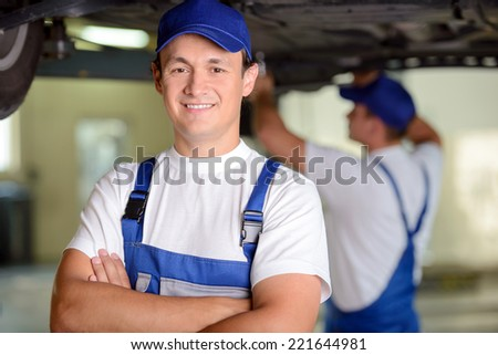 Mechanics at work shop. Confident young mechanic standing with his arms crossed and smiling at camera while another one working on the background - stock photo