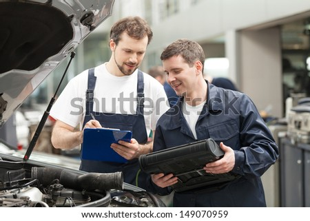 Mechanics at work shop. Two confident mechanics discussing something while one of them holding a clipboard