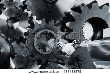 mechanics, engineers with large cogwheels and gear machinery - stock photo