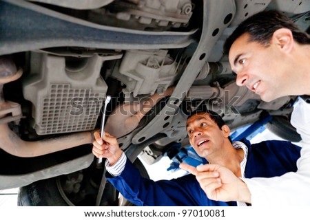 Mechanics fixing a car underneath at the garage - stock photo