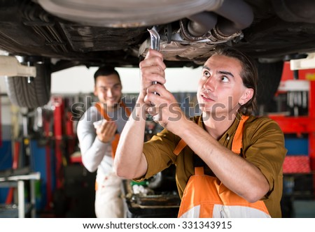 Mechanics in orange and white coveralls are repairing exhaust system of a car. Workmen replacing a muffler on a sedan - stock photo