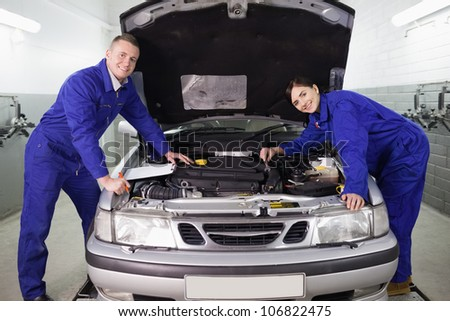 Mechanics leaning on a car in a garage - stock photo