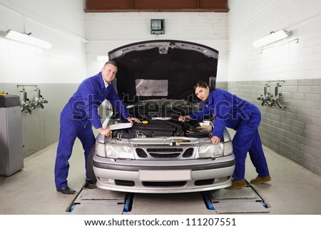 Mechanics leaning on a car looking at camera in a garage - stock photo