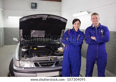 Mechanics next to a car a garage