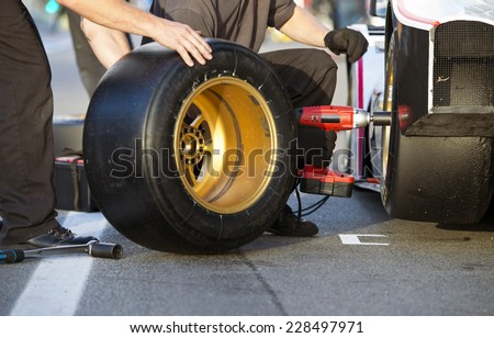Mechanics of a pit crew changing the slicks of a race car during a pitstop - stock photo