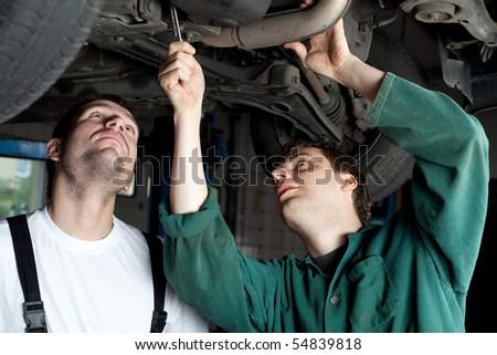 Mechanics repairing car in garage under the car. - stock photo