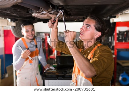 Mechanics repairing exhaust system on a lifted up car at a automotive service station - stock photo