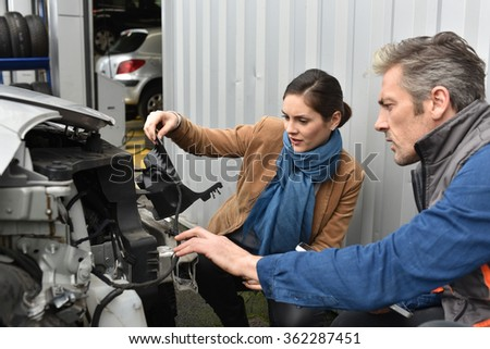 Mechanics showing customer what is to repair on car - stock photo