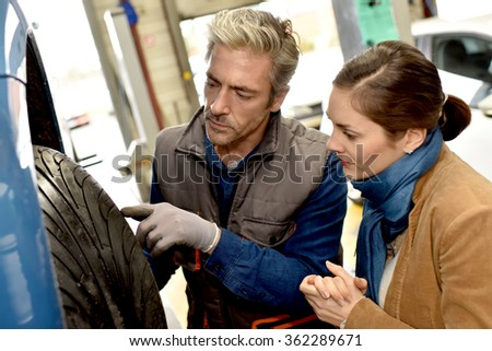 Mechanics showing customer what is wrong with car tire - stock photo