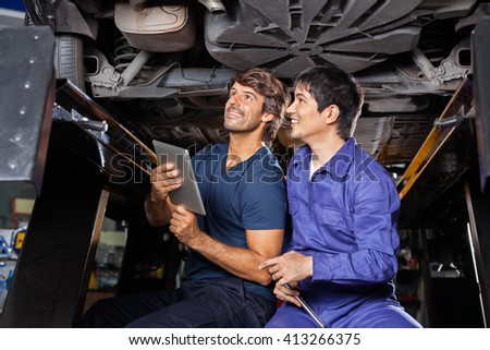 Mechanics With Digital Tablet Examining Underneath Car - stock photo