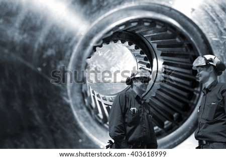 mechanics, workers in front of giant gears axle - stock photo
