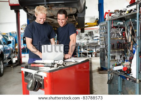 Mechanics working on laptop in auto repair shop - stock photo