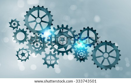 Mechanism of metal gears and cogwheels on blue background - stock photo