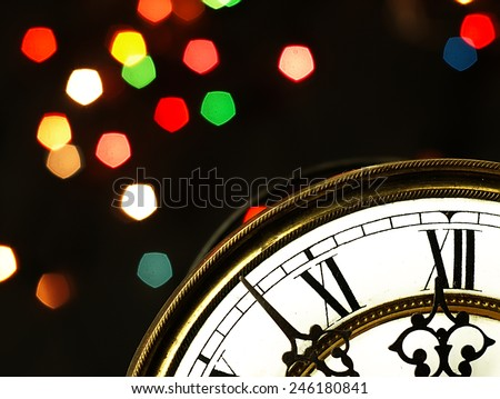 Mechanism of old clock on black background. Clock face and hands showing five minutes to midnight. - stock photo