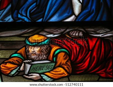 MECHELEN, BELGIUM - NOVEMBER 4, 2016: Stained Glass window depicting a heretic, in the Cathedral of Saint Rumbold in Mechelen, Belgium.