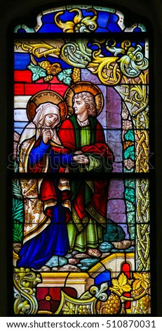 MECHELEN, BELGIUM - NOVEMBER 4, 2016: Stained Glass window depicting Mother Mary and Saint John the Apostle on Good Friday, in the Cathedral of Mechelen, Belgium.