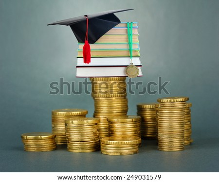 Medal for achievement in education with diploma, hat and books standing on stack of coins on gray background - stock photo