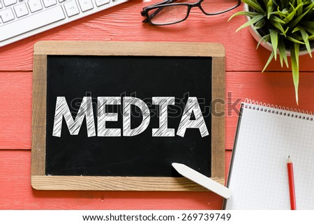 Media word Handwritten on blackboard. Media word Handwritten with chalk on blackboard, keyboard,notebook,glasses and green plant on wooden background - stock photo