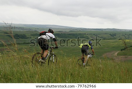 MEDIAS, ROMANIA, -JUNE 11: Two unidentified mountainbikers during competition on June 11, 2011 at Medieval Mountainbike Marathon in Medias, Romania. - stock photo