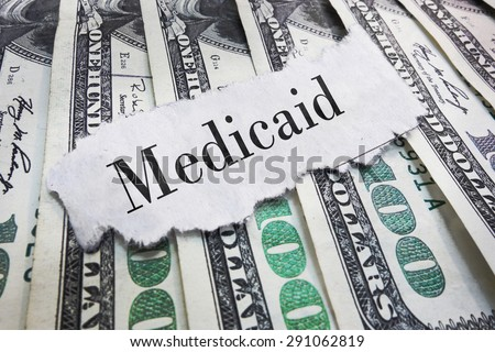 Medicaid torn newspaper headline on cash                                - stock photo