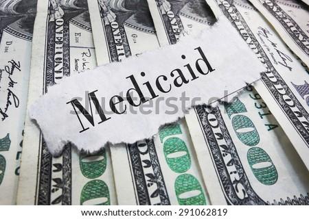 Medicaid torn newspaper headline on cash                                - stock photo