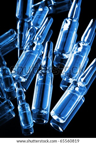 Medical ampoules scattered on black background - stock photo