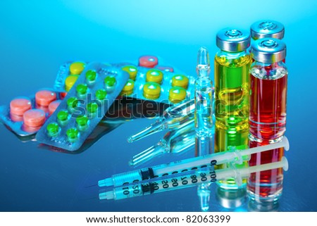 medical ampoules, tablets and syringe on blue background - stock photo