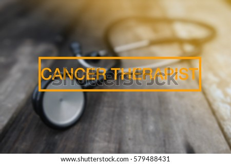Medical And Health Concept - Stethoscope on vintage wooden table with CANCER THERAPHY word. tone image.