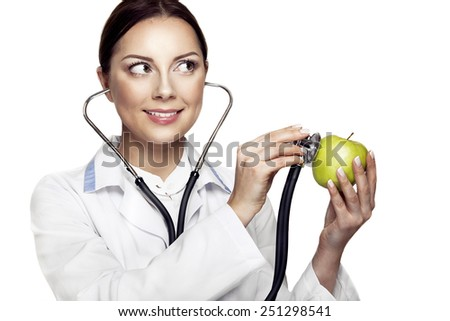 Medical and healthy lifestyle concept. Attractive happy female doctor holding green apple and stethoscope and smiling. - stock photo
