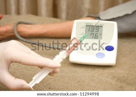 medical assistance to patient with high blood pressure by giving an injection - stock photo