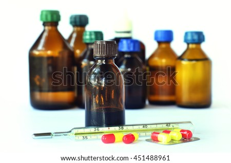 Medical bottles for mixtures, syrups and health-care oils with thermometer on white background - stock photo