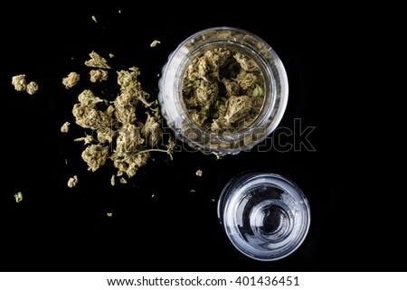 Medical cannabis buds in an open glass jar with marijuana flowers scattered aside and transparent lid on black background directly from above - stock photo