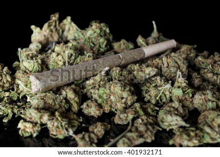 Medical cannabis rolled joint on dried marijuana buds on black background from side - stock photo
