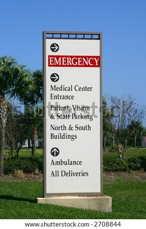 "Medical center directory sign with the word ""Emergency"" prominently displayed. Palm trees and landscaped green lawn visible.