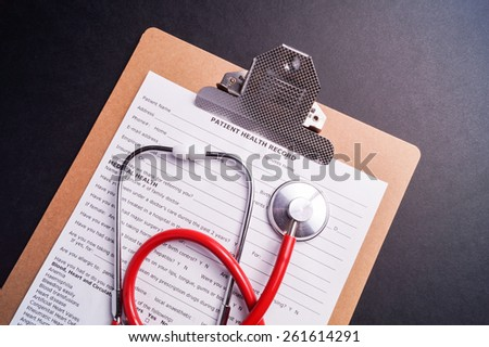 Medical Chart and stethoscope isolated on black background - stock photo