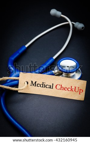 Medical check up word in paper tag with stethoscope on black background - health concept. Medical conceptual - stock photo